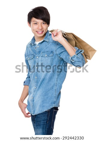 Asian man holding up with paper bag - stock photo