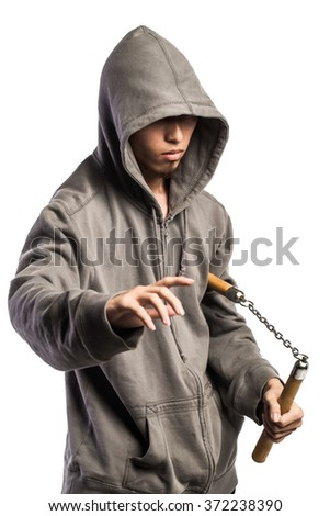 asian man in a hood is using a nunchaku - stock photo