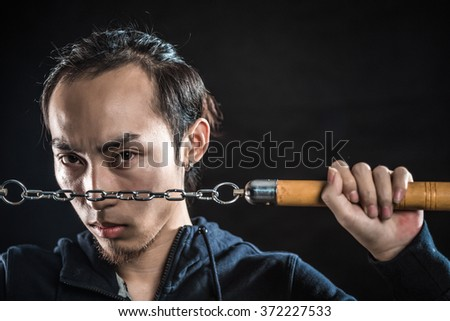 asian man in a hood is using a nunchaku isolated on black