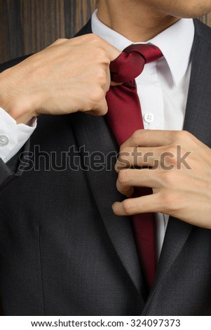 Asian man in a suit correcting his red necktie