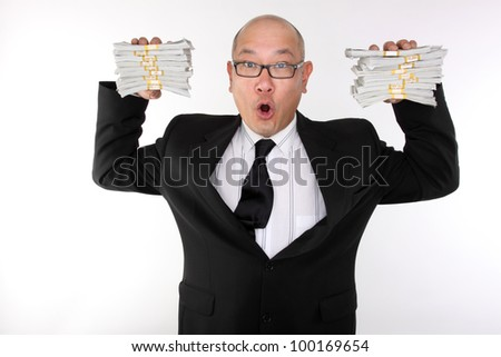 Asian man in a suit with bundles of cash.