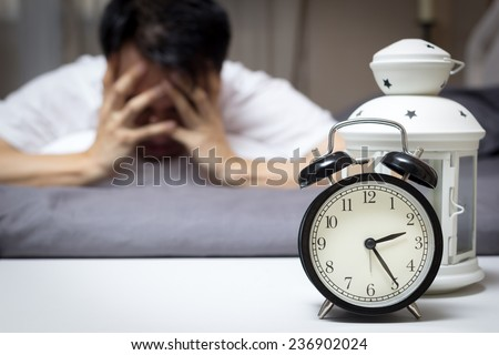 Asian man in bed suffering insomnia and sleep disorder thinking about his problem at night - stock photo
