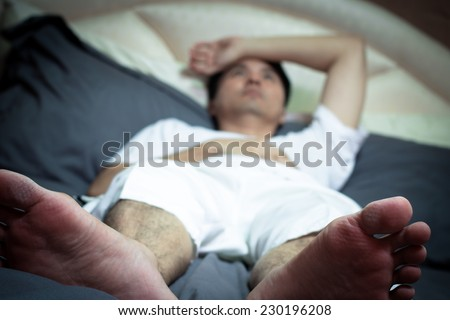 Asian man in bed suffering insomnia and sleep disorder thinking about his problem / focus to feet - stock photo
