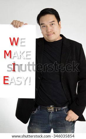 Asian man in black suit with WE MAKE IT EASY! message on white board ,on gray background.