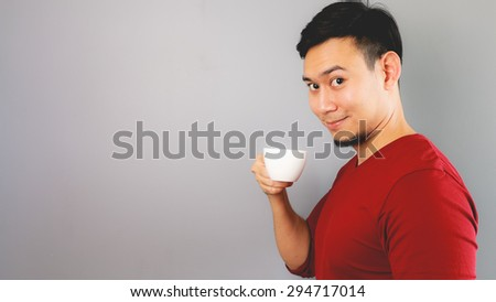 Asian man in red T-shirt is drinking a cup of coffee, tea.