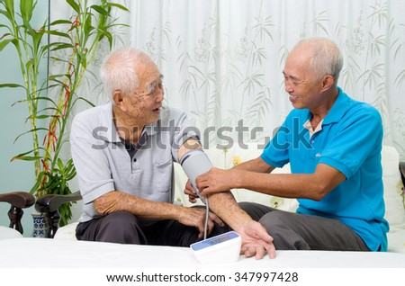 Asian man is checking his father's blood pressure. - stock photo