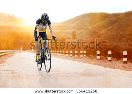 Asian man is cycling road bike in the afternoon on the asphalt road at outdoor nature.