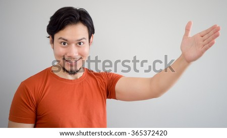 Asian man is presenting a product or idea. - stock photo