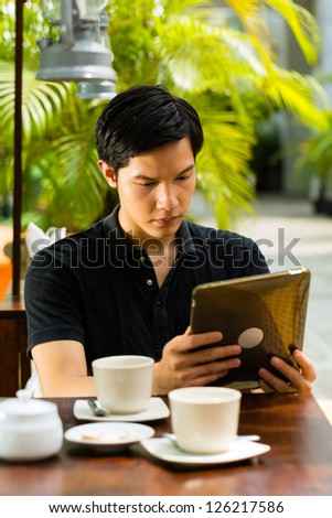 Asian man is sitting in a bar or cafe outdoor and is surfing the internet with a tablet computer
