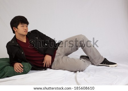 Asian man laying down and looking to the right thoughtfully and seriously
