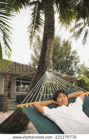 Asian man laying in hammock - stock photo