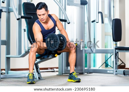 Asian man lifting hand weight at gym