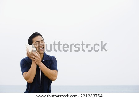 Asian man listening to conch shell - stock photo