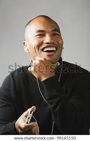 Asian man listening to mp3 player - stock photo