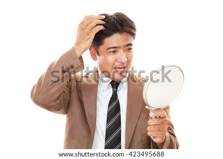 Asian man looking at his face in mirror