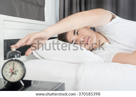 Asian man lying on the bed and stopping alarm clock in morning