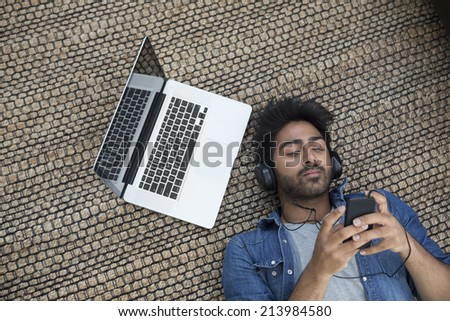 Asian man lying on the floor at home with laptop and phone. Above view - stock photo