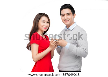 Asian man makes present to his lovely sweetheart. Young man giving a gift. Cheerful young couple man and woman at home offering to each other gifts for lover's valentine day - stock photo