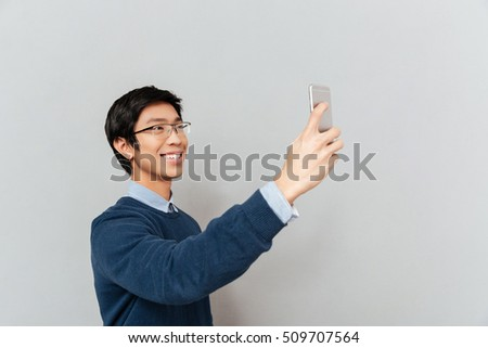 Asian man photographs on the phone. selfie