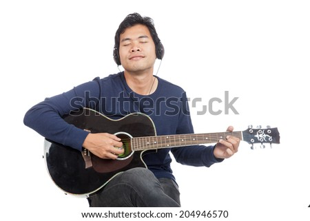 Asian man playing guitar with headphone isolated on white background - stock photo