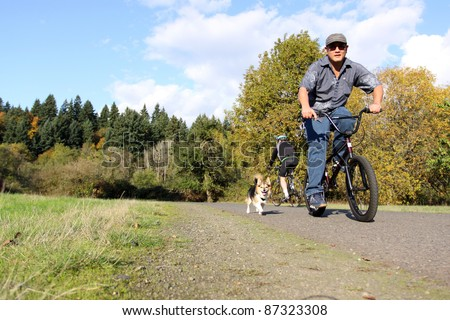 Asian man riding bicycle with pet dog.
