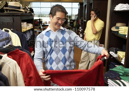 Asian man selecting shirt with person in background at clothing store - stock photo