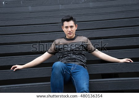Asian man sits and acts at outdoor.