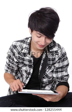 Asian man sitting and using touch pad with smile, casual wear - stock photo