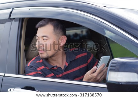 Asian man sitting in car holding mobile phone and looking back