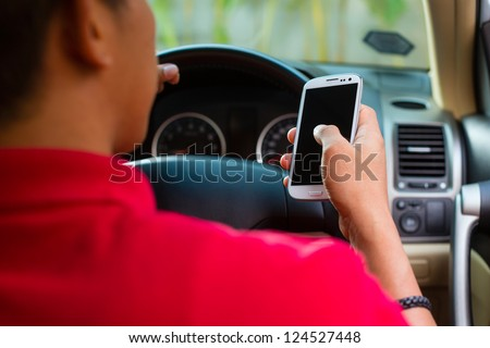 Asian man sitting in car with mobile phone in hand texting while driving - stock photo