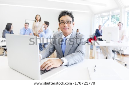 Asian Man Smiling While Working on Laptop in Office - stock photo