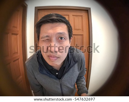 Lovely Asian Man Standing And Waiting In Front Of Door See Through The Peephole Of  Door