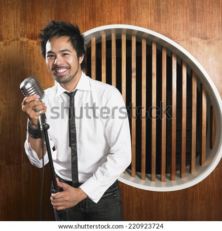 Asian man standing at microphone - stock photo