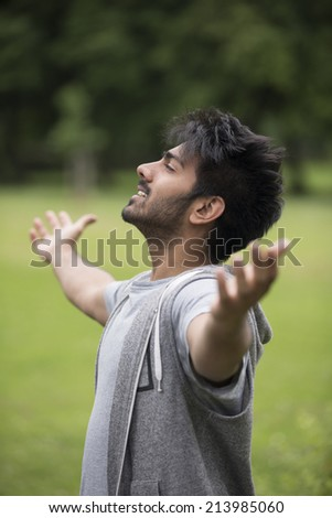 Asian man standing with arms raised outdoors. Concept about freedom, faith and celebration. - stock photo