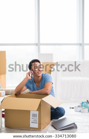 Asian man talking on the phone after unpacking in new apartment - stock photo