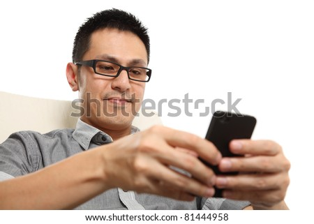 Asian man typing a message on mobile phone. Isolated on white background.