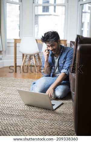 Asian Man using a laptop and talking on phone at home in the lounge. - stock photo