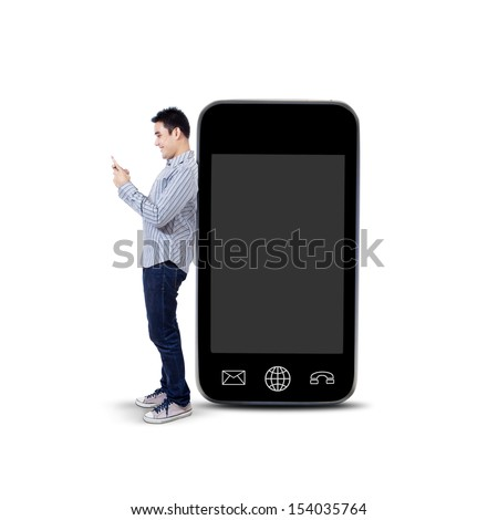 Asian man using a mobile phone and standing next to big smartphone isolated on white background - stock photo