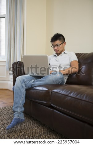 Asian man using Laptop at home in the lounge. - stock photo
