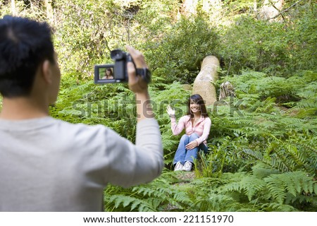 Asian man video recording girlfriend in woods - stock photo