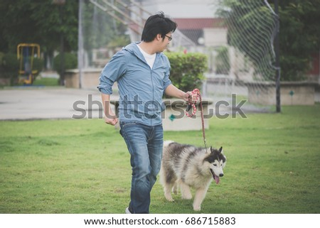 Asian man walking with a siberian husky don in the park