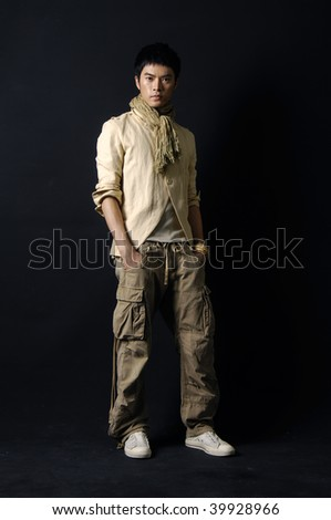 Asian man walking with his hands in pockets