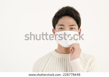 Asian man wearing a face mask - stock photo