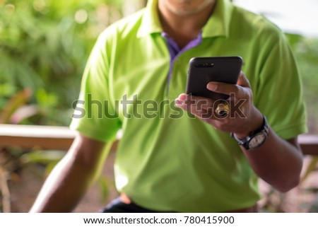 Asian man wearing a green t-shirt using smartphone while waiting his friend at gas station.