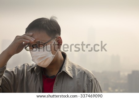 Asian man wearing mouth mask against air pollution - stock photo