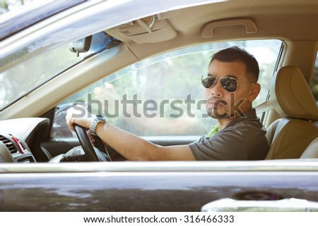 Asian man wearing sunglasses driving his car and looking out of the car, process in vintage tone