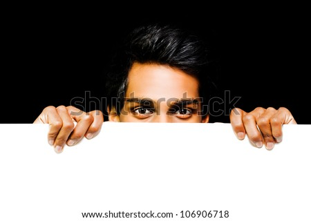Asian man with an amused expression in his eyes peeping over the top of a blank white placard or banner as he announces a surprise deal on discounted or promotional products - stock photo