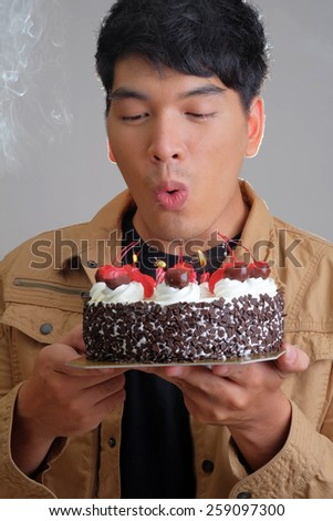Asian man with birthday ice-cream cake on fire - stock photo