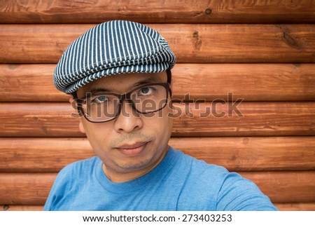 Asian man with glasses wearing hat in front of wood wall