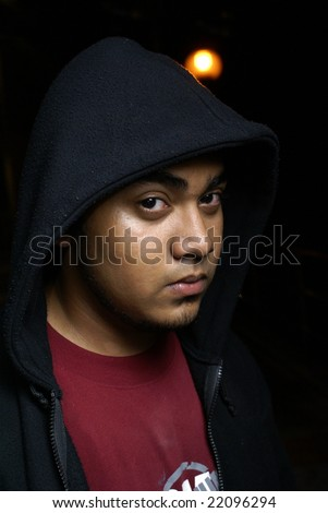 Asian man with hood portrait at night